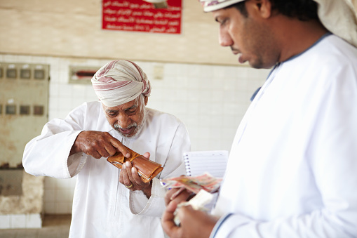 Customer paying stall holder in Rial in morning fish market, Muttrah, Muscat, Oman, Middle East